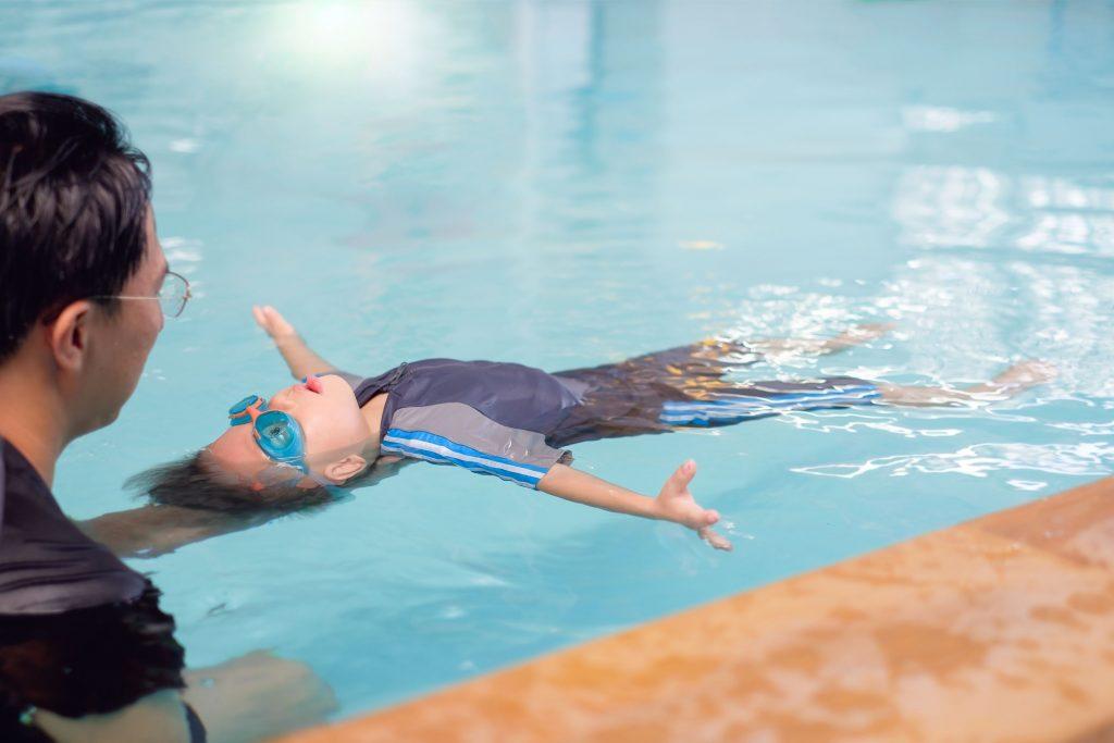 teach kids to swim young in swimming pool